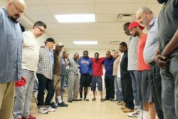 Men huddle to pray at the close of an Overcomers support group meeting